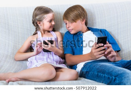 Smiling little girl and teenage boy burying in mobile phones sitting on the sofa