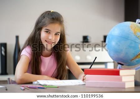 Smiling little girl doing her homework - stock photo