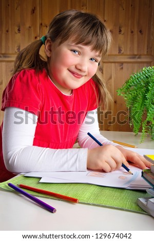 Smiling little girl drawing with color pencils at her desk