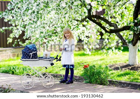 smiling little girl driving toy stroller in the flowering garden  - stock photo