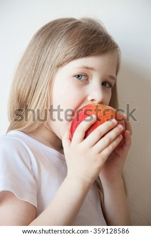 Smiling little girl eating a big red apple, neutral background - stock photo
