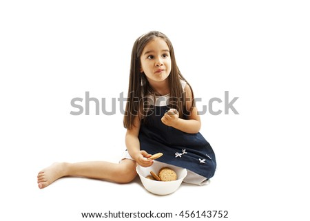 Smiling little girl eating cookie or biscuit, looking up. Isolated on white background.   - stock photo
