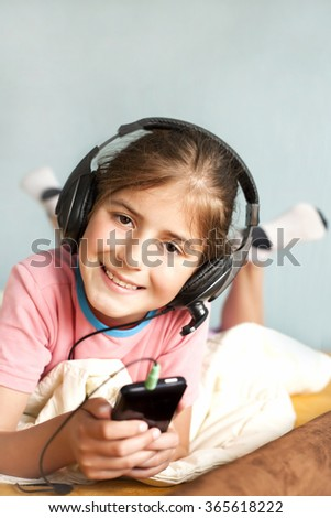 smiling little girl enjoys music - stock photo