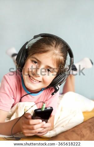 smiling little girl enjoys music - stock photo