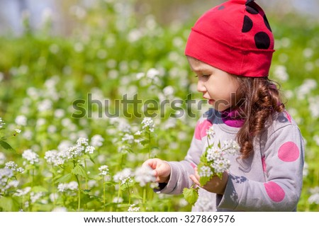 Smiling little girl having fun at park early spring. Bright green grass and wild white flowers as a background. - stock photo