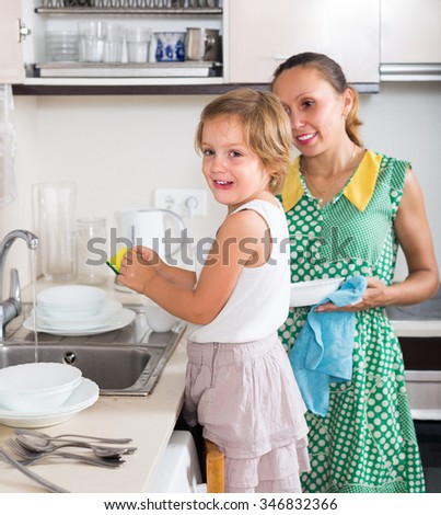 Smiling little girl helping mother washing dishes in the kitchen. Focus on girl