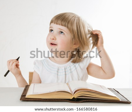 Smiling little girl holding a pen and looking up, neutral background