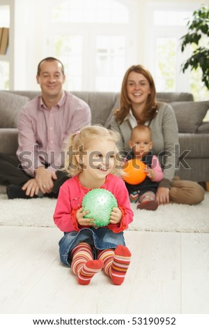 Smiling little girl holding ball at home with family in background.