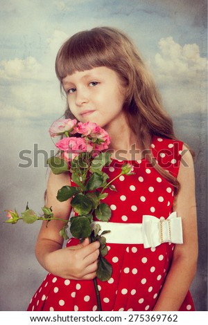 Smiling little girl holding flowers. Closeup. Photo in retro style with old textured paper. - stock photo
