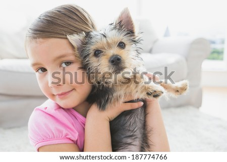 Smiling little girl holding her yorkshire terrier puppy at home in the living room - stock photo