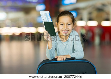 smiling little girl holding passport and boarding pass at airport  - stock photo