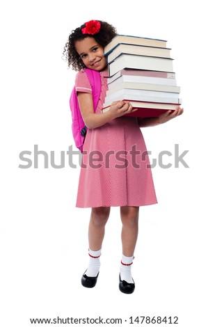 Smiling little girl holding pile of school books - stock photo