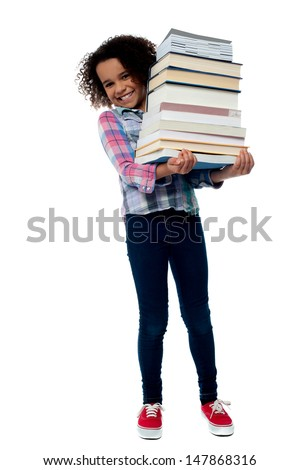 Smiling little girl holding stack of school books - stock photo