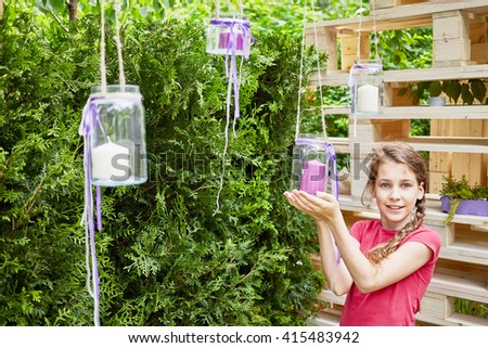 Smiling little girl holds in hands hanging glass jar with candle inside in alcove at park. - stock photo