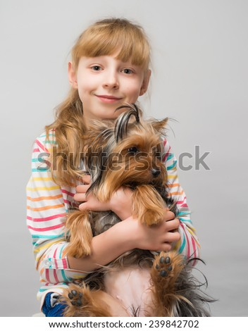 smiling little girl hugging a yorkshire terrier dog in an outdoor setting - stock photo