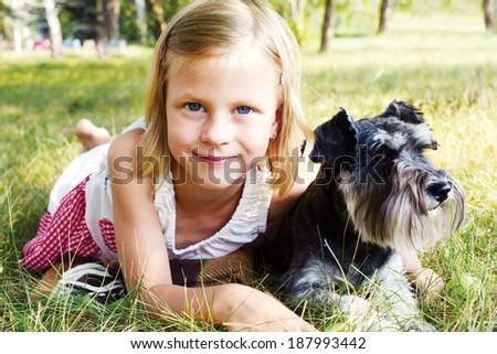 smiling little girl hugging her dog lying on green grass in summer day - stock photo