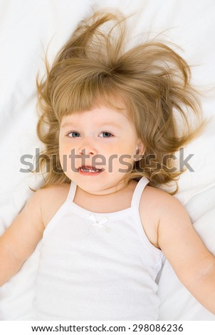 Smiling little girl in a bed - stock photo