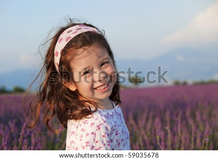 Smiling little girl in a lavender field - stock photo