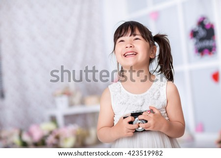 smiling little girl in a white dress  holding an old camera. child taking pictures on an old camera - stock photo