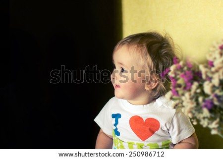 smiling little girl in a white T-shirt looks away - stock photo