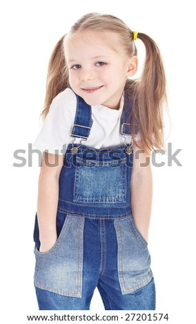 Smiling little girl in blue jeans overalls holding hands in her pockets