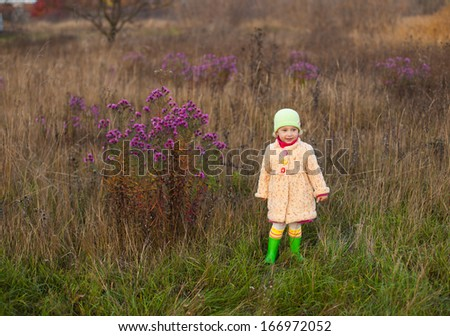 Smiling little girl in bright colourful clothes in autumn