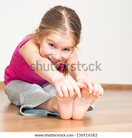 smiling little girl in pink engaged in fitness - stock photo