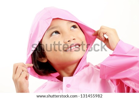Smiling little girl in pink raincoat looking upward.Close up. - stock photo