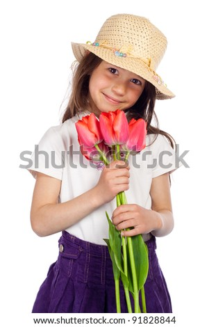 Smiling little girl in straw holding in hands red tulips