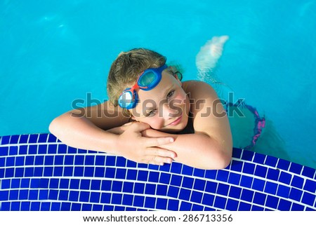 Smiling little girl in swimming goggles relaxing in the swimming pool - stock photo