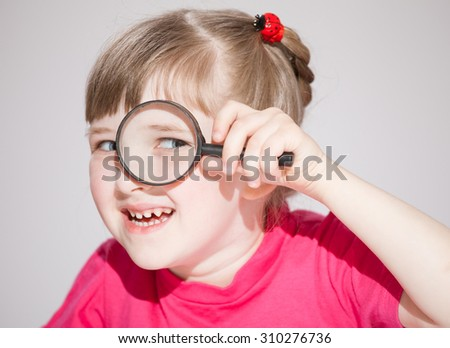 Smiling little girl looking through a loupe, neutral background - stock photo
