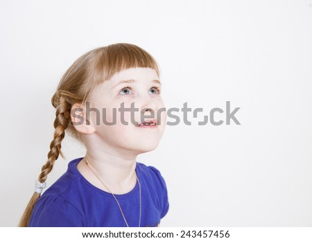 Smiling little girl looking up, white background - stock photo