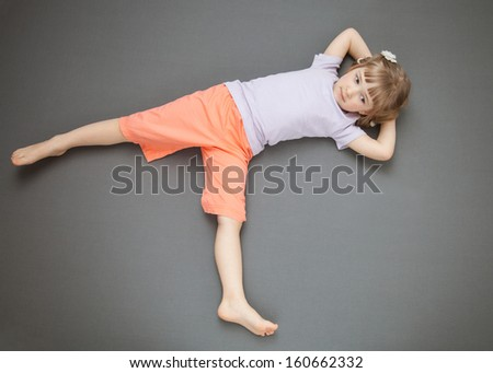 Smiling little girl lying on the floor, grey background - stock photo