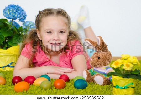 Smiling little girl lying with Easter eggs and flowers on green carpet