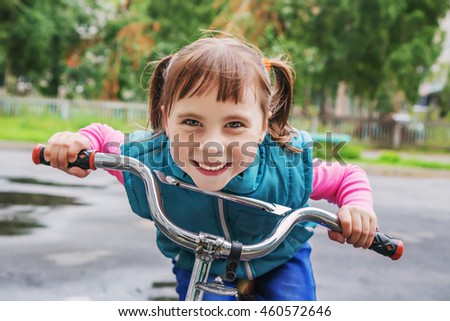 Smiling little girl on a bicycle.