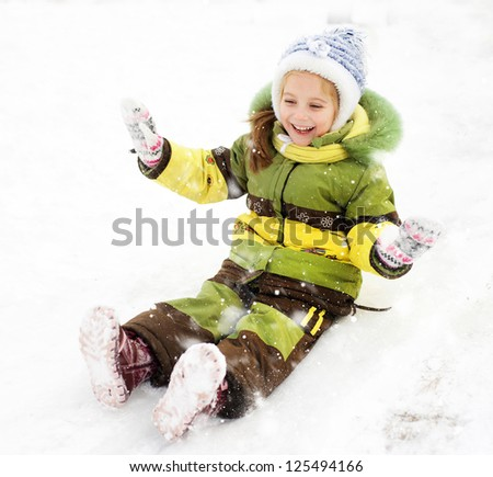 Smiling Little girl on the ice slide - stock photo