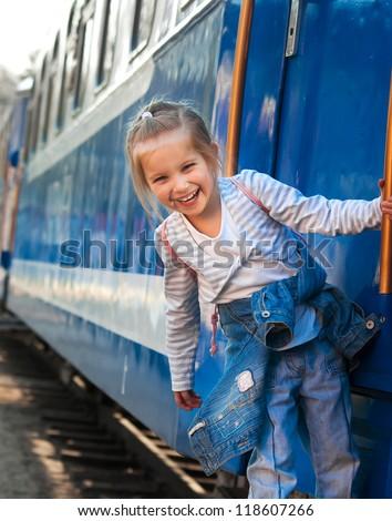 Smiling little girl on train - stock photo