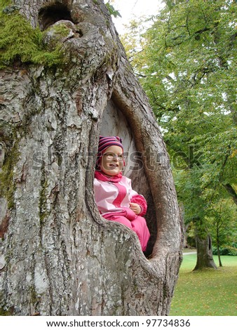 Smiling little girl one years old wearing glasses in pink overalls sits in big hollow tree - stock photo
