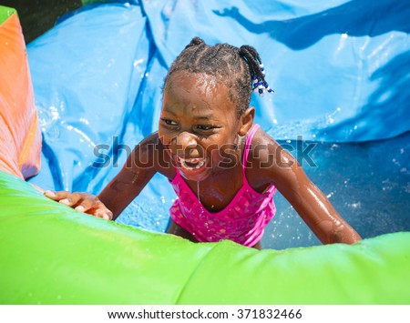 Smiling little girl playing outdoors on an inflatable bounce house water slide - stock photo