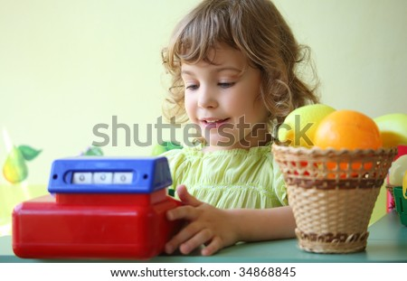 smiling little girl plays shop