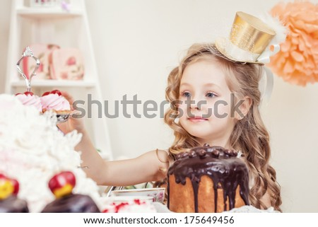 Smiling little girl posing in golden hat