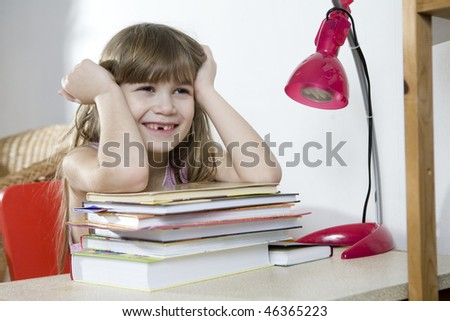 smiling little girl put her hand on book - stock photo