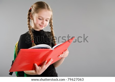Smiling little girl reading a book - stock photo