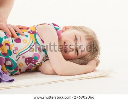 Smiling little girl resting on the floor, white background - stock photo