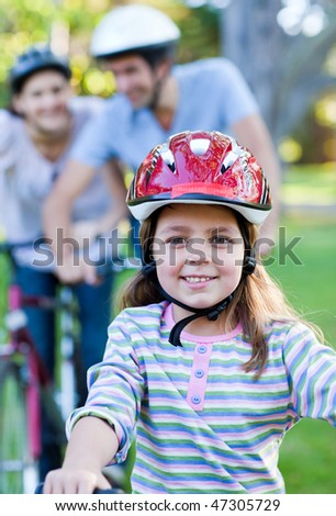 Smiling little girl riding a bike in a park - stock photo