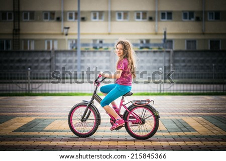 Smiling little girl riding bicycle in city in rain. - stock photo