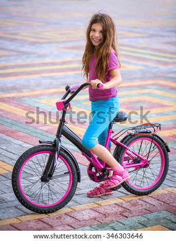 Smiling little girl riding bicycle in city park. - stock photo