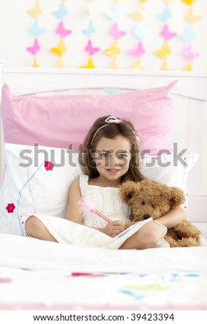 Smiling little girl sitting in bed writing in a notebook - stock photo