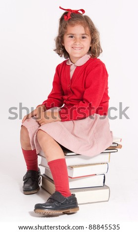 Smiling little girl sitting on a pile of books - stock photo