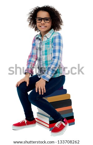 Smiling little girl sitting on a stack of books over white background. - stock photo